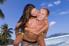 Una ragazza dà al suo amante un bacio sulla spiaggia Immagine Stock Libera da Diritti