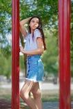 Una ragazza d'avanguardia in pantaloni a vita bassa alla moda copre su uno sfondo naturale vago Modo, all'aperto, concetto della  fotografie stock