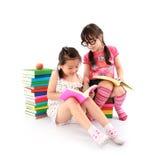 Una ragazza dei due allievi che legge il libro Immagini Stock