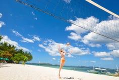 Una ragazza del bikini che gioca pallavolo sulla spiaggia bianca fotografia stock libera da diritti
