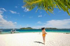 Una ragazza del bikini tiene la noce di cocco sulla spiaggia bianca Immagine Stock