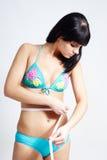 Una ragazza del brunette che misura la sua vita Fotografie Stock