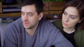 Una ragazza del cameriere che indossa un grembiule accetta un ordine da tre amici con capelli scuri che si siedono in un ristoran archivi video