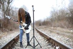 Una ragazza del musicista della roccia in un bomber con una chitarra Immagine Stock Libera da Diritti