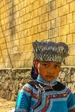 Una ragazza del villaggio di minoranza di Hani che indossa gli ornamenti tradizionali del copricapo immagini stock libere da diritti