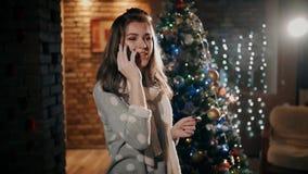 Una ragazza del yound sta parlando sul telefono sul primo dell'anno, tenente una stella filante archivi video
