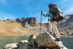 Una ragazza della viandante in occhiali da sole con uno zaino ed i bastoni dell'inseguimento aumenta ad un'alta roccia contro lo  Immagine Stock Libera da Diritti