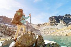 Una ragazza della viandante in occhiali da sole con uno zaino ed i bastoni dell'inseguimento aumenta ad un'alta roccia contro lo  Fotografia Stock Libera da Diritti