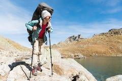 Una ragazza della viandante in occhiali da sole con uno zaino ed i bastoni dell'inseguimento aumenta ad un'alta roccia contro lo  Immagine Stock