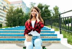 Una ragazza dello scolaro di estate in parco si siede su un pattino Chiamate ai genitori ed alle amiche Sorrisi felici Online immagine stock
