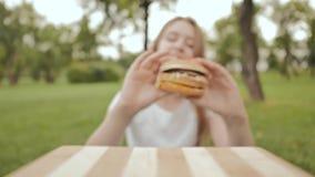 Una ragazza dello studente prende un hamburger cucinato con le sue mani Lo mangia all'aperto Estate ricreazione video d archivio