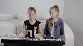 Una ragazza di due bambini che gioca il piano a casa, amici felici archivi video