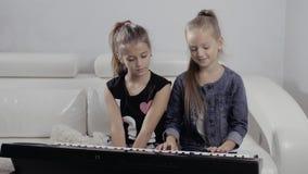 Una ragazza di due bambini che gioca il piano a casa, amici felici stock footage