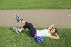Una ragazza di pattinaggio a rotelle in parco che rollerblading sopra immagini stock libere da diritti