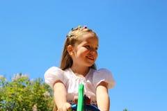 Una ragazza di sette anni su un fondo di cielo blu Fotografia Stock