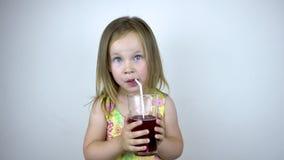 Una ragazza di tre anni del bambino beve il succo da una tazza di vetro con una paglia Su una priorit? bassa bianca stock footage
