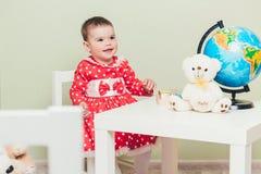 Una ragazza di un anno in un vestito rosso sta sedendosi ad una tavola con un libro, un globo e un orsacchiotto Fotografia Stock Libera da Diritti