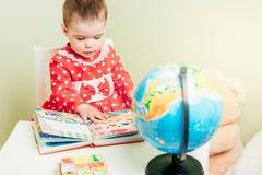 Una ragazza di un anno in un vestito rosso sta sedendosi ad una tavola con un libro, un globo e un orsacchiotto Fotografie Stock