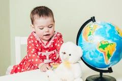 Una ragazza di un anno in un vestito rosso sta sedendosi ad una tavola con un libro, un globo e un orsacchiotto Immagini Stock