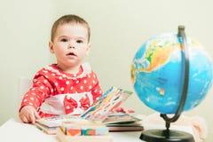 Una ragazza di un anno in un vestito rosso sta sedendosi ad una tavola con un libro, un globo e un orsacchiotto Immagine Stock