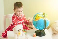 Una ragazza di un anno in un vestito rosso sta sedendosi ad una tavola con un libro, un globo e un orsacchiotto Fotografie Stock Libere da Diritti