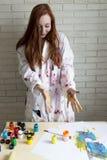 Una ragazza dipinge l'immagine con i colori facendo uso delle sue proprie mani immagini stock libere da diritti