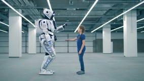 Una ragazza e un robot stanno toccando le palme a vicenda video d archivio