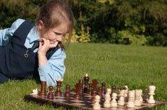 Una ragazza e una scacchiera Fotografia Stock