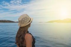 Una ragazza esamina il tramonto nel mare Fotografia Stock