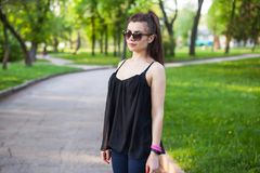 Una ragazza esamina la macchina fotografica mentre cammina nel parco immagine stock libera da diritti