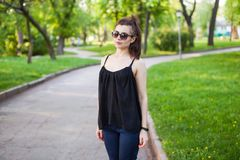 Una ragazza esamina la macchina fotografica mentre cammina nel parco fotografie stock