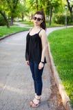 Una ragazza esamina la macchina fotografica mentre cammina nel parco fotografia stock