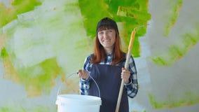 Una ragazza fa le riparazioni La ragazza con il rullo dipinge le pareti La ragazza fa le riparazioni ed i sorrisi Verniciatura stock footage