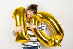Una ragazza facile da dieci compleanni con i palloni dorati Immagine Stock