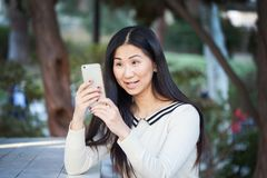 Una ragazza felice che guarda fisso sul suo telefono con entusiasmo Fotografie Stock