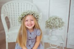 Una ragazza felice con una corona floreale sta ghignando Immagini Stock
