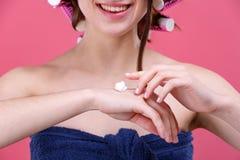 Una ragazza felice mette una crema cosmetica bianca sulle sue mani Su un fondo rosa Primo piano Fotografia Stock Libera da Diritti