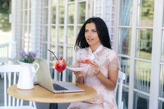 Una ragazza felice s che aspetta i suoi amici in un caffè, guarda qualcosa in suo computer portatile, ordinato un dessert, vuole  immagini stock