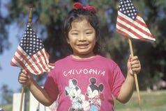 Una ragazza Filippino-americana che tiene le bandiere dell'America, Los Angeles, CA immagine stock