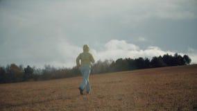 Una ragazza funziona attraverso il campo stock footage