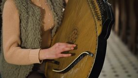 Una ragazza gioca su una bandura ucraina tradizionale dello strumento nella chiesa video d archivio