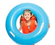Una ragazza in giubbotto di salvataggio ed occhiali di protezione con l'anello di gomma Immagini Stock