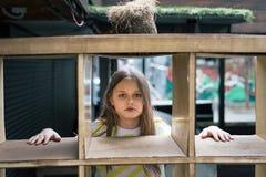 Una ragazza graziosa che guarda fuori da dietro una struttura a forma di gabbia fotografia stock libera da diritti
