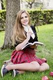 Una ragazza graziosa che legge un libro, imparante Fotografie Stock Libere da Diritti