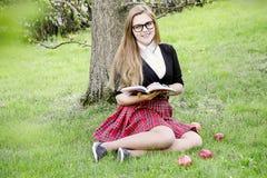 Una ragazza graziosa che legge un libro, imparante Immagine Stock