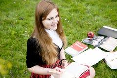 Una ragazza graziosa che legge un libro, imparante Fotografie Stock