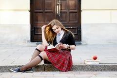 Una ragazza graziosa che legge un libro, imparante Immagini Stock Libere da Diritti
