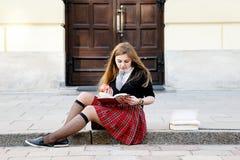 Una ragazza graziosa che legge un libro, imparante Fotografia Stock