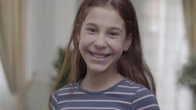 Una ragazza graziosa che si nasconde dietro il pallone giallo con un fronte felice dipinto su poi lo mette giù Il bambino sta sor stock footage