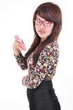 Una ragazza graziosa che sorride e che tiene un telefono cellulare Fotografie Stock Libere da Diritti